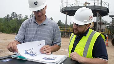 Doug Aholt reviews mine ventilation plans with a colleague at Big Bear Vent Shaft.